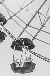 Ferris wheel booths in black and white image. The cabin of the Ferris wheel against the sky on top.Background image of the Ferris wheel. vertical image