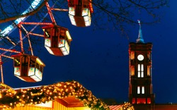 Ferris Wheel in Night Christmas Market at Town Hall in Winter Berlin, Germany. German street Xmas and holiday fair in European city or town. Advent Decoration and Stalls with Crafts Items on Bazaar