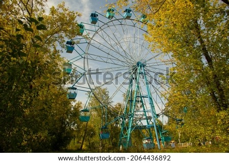 Ferris wheel in the autumn forest. Scenic view from the forest to the Ferris wheel.