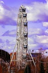 Ferris wheel in the city of Tyumen in Russia. Creative processing in purple tones.