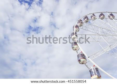 Ferris wheel in the cloudy blue sky #451558054