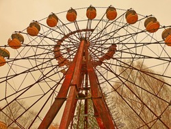 Ferris wheel in the park of the abandoned Pripyat ghost town in the Chernobyl exclusion zone, old amusement park at autumn season, sad depression mood, gloomy sky, desolate urban landscape, apocalypse
