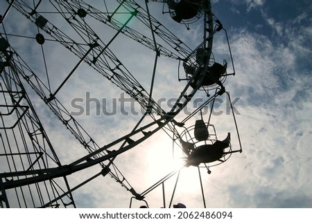 Ferris wheel on a background of blue sky. Attraction in the park close-up