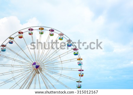 Ferris wheel on cloudy sky background