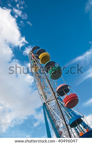 Ferris wheel over dreamy summer cloudy sky