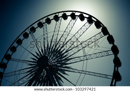 ferris wheel silhouette backlit by moonlight