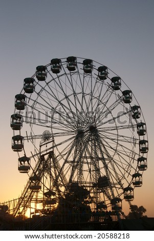 Ferris wheel silhouetted against the darkening sky as the sun sets over the Pushkar fair in Rajasthan, India - stock photo