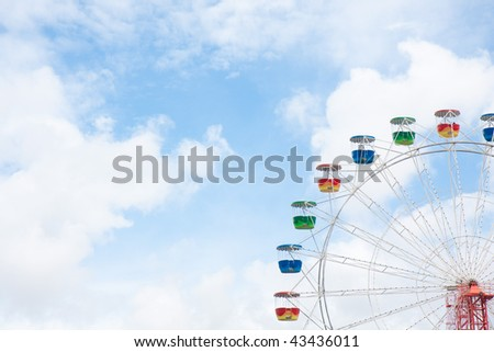 Ferris wheel with blue sky and clouds