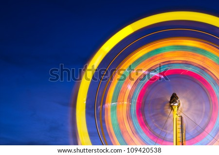 Stock Photo Ferris wheel with motion blurred lights with copy space