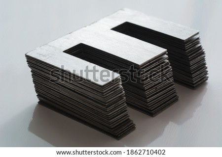 Ferromagnetic metal core for high energy efficient transformer. Ferrite transformer for switching power supply. Selective focus, shallow depth of field. Foto stock ©