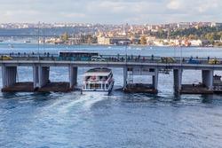 Ferry boat ship passes under the Unkapani Bridge at Golden Horn bay, Istanbul, Turkey
