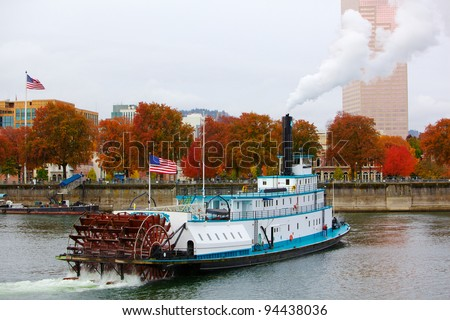 Ferry or steam boat in Portland on Willamette river under steam with two American flags on an overcast day