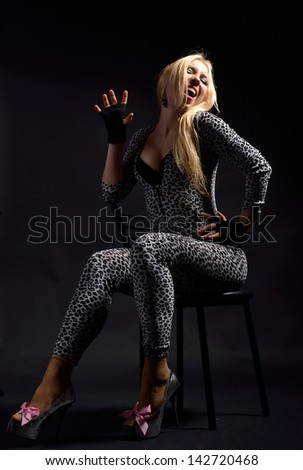Fervent woman is imitating a cat. She is sitting on the chair in the dark. She is wearing a spotty slinky catsuit and high heels with pink bows.