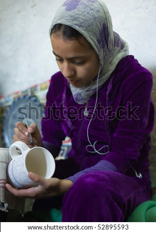FES - APRIL 17: Islamic girl is painting ceramics in a pottery in Fes April 17, 2010 in Fes, Morocco.