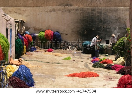 FES, MOROCCO - JUNE 9: Men coloring dried hay with bright dye on June 9, 2008 in Fes, Morocco. The dye used is very poisonous and often creates health issues for workers