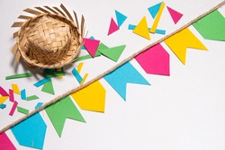 Festa Junina theme background. Little flags hanging on a rope. Confetti and a tradicional brazilian straw hat. White background. Mockup invitation card.