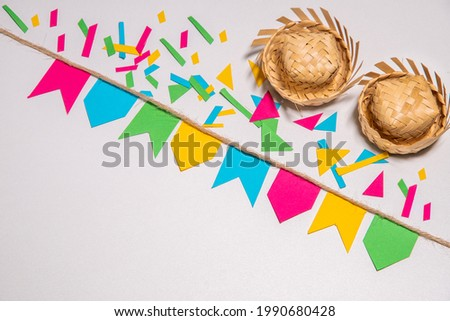 Festa Junina theme background. Little flags hanging on a rope. Confetti and two tradicionals brazilian straw hats. White background. Mockup invitation card. Foto stock ©