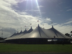 Festival tent in an empty field with the sun shining
