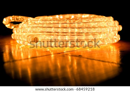 festive abstract of coiled rope lighting on a reflective hardwood floor