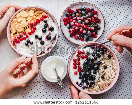 Festive and healthy breakfast for loved ones. Vintage bowls, cornflakes, granola, yogurt, fresh berries and hands of a young couple. Close-up, top view. Concept of healthy and delicious food #1262111566