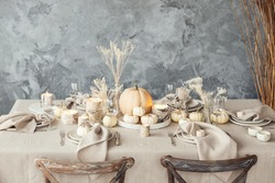 Festive autumn and winter holiday table setting with white pumpkins and candles. Thanksgiving and Christmas table concept. Family dinner.