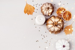 Festive Autumn concept. Decorative pumpkins, golden confetti and dry leaves on gray background. Zero waste decor.