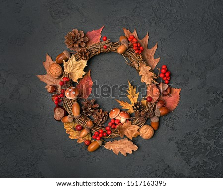 Festive autumn Thanksgiving wreath with mushrooms, fall leaves, red berries, acorns on dark background. autumn holiday, fall, thanksgiving, halloween concept. Flat lay, top view, copy space #1517163395