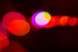 Festive background. Bokeh light. Blur neon glow. Defocused bright red orange pink round flecks abstract pattern on dark decorative wallpaper with empty space.