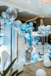 Festive background decoration letters saying one and white blue balloons in studio. Baby birthday theme with teddy bear. Baby Boy. Cake Smash first year concept. birthday greetings. Candy bar.