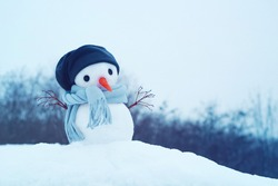 Festive background with a lovely snowman. Christmas card with small snowman in a cap and a scarf on snow in the winter, copy space.