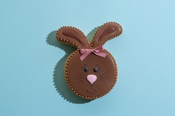 Festive bakery food. Cute bunny pastry. Sweet gift. Holiday party decor. Pretty rabbit gingerbread cookie with chocolate icing painted smiling snout isolated on blue copy space.