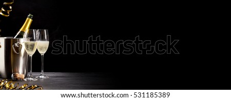 Festive banner with romantic champagne in two elegant flutes alongside a bottle chilling on ice over a dark panoramic background with copy space