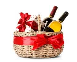 Festive basket with bottles of wine and gift on white background