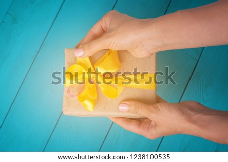 Festive blue background. The receipt of gifts. Female hands holding a gift. The girl unpacks the gift. The woman gives you a gift. Yellow bow on the gift.