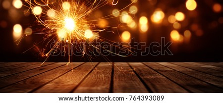 Festive bokeh background with burning sparkler and wooden stage for a christmas decoration #764393089
