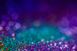 Festive bokeh glitters background, abstract shiny backdrop with circles,modern design overlay with sparkling glimmers. Blue, purple and green backdrop glittering sparks with glow effect