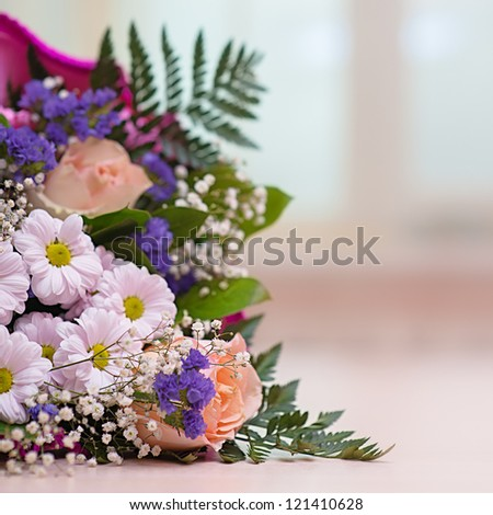 Festive bouquet of different flowers on table against window in the room.