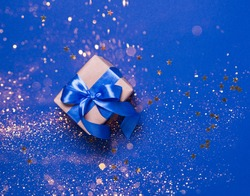 Festive box in gold packaging with a satin bow on a blue background
