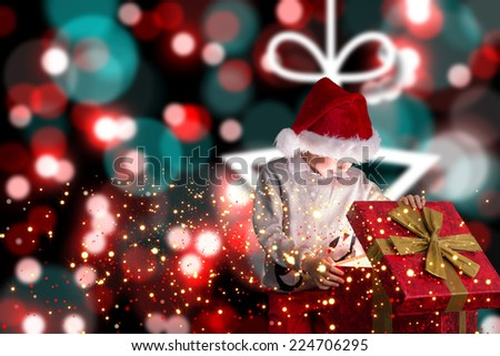 Festive boy opening gift against blurred christmas background