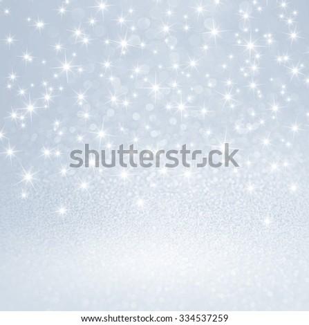 Festive bright lights and shiny stars on glitter silver background
