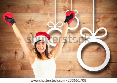Festive brunette in boxing gloves cheering against christmas decorations over wood