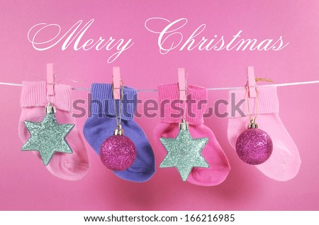 Festive childrens baby stockings hanging from pegs on a line with Merry Christmas greeting and ornaments decorations against a pretty pink background. Baby\'s First Christmas or Young Family greeting.