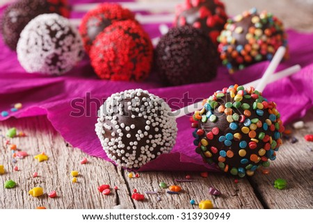 Festive chocolate cake pops with candy sprinkles close-up on the table. horizontal