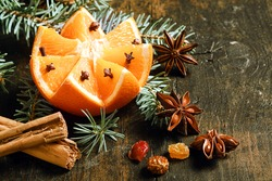 Festive Christmas background with a fresh orange cut in a fancy pattern studded with cloves on a fresh pine branch surrounded by star anise and stick cinnamon spice and nuts on a rustic background