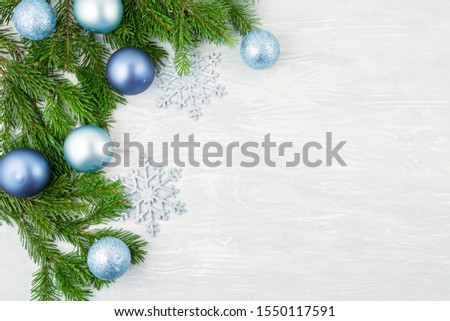 Festive christmas background with blue and silver xmas decoration and xmas tree over the light wooden background