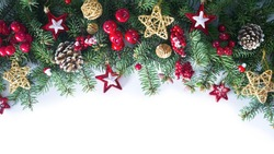 Festive Christmas border, isolated on white background. Fir green branches are decorated with gold stars, fir cones and red berries. Close-up, copy space.