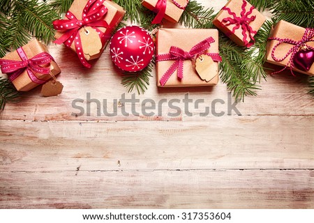 Festive Christmas border with gifts tied with red ribbon, matching red baubles and fresh pine foliage over rustic wood with copyspace for your seasonal greeting