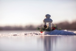festive christmas card candle burning in an elegant spruce wreath stands in the park on the ice