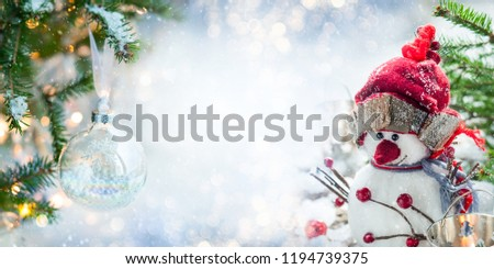 Festive Christmas card with snowman, Christmas bauble and fir branches  on winter background. #1194739375
