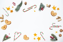 Festive Christmas composition of fir branches, berries, nuts, candy canes, cookies and stars on a white background. Colorful Christmas ornament with space for text flat lay